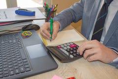 Hand mit Rechner Finanz- und Buchhaltungsgeschäft Junger Geschäftsmann Calculating Finance Bills im Büro Lizenzfreies Stockbild