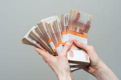 Hand mit Rechnungen der russischen Rubel auf weißem Hintergrund lizenzfreie stockfotos