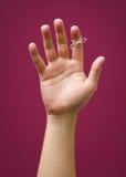 Hand mit remider Schnur lokalisiert auf rotem purpurrotem Pflaumenhintergrund Lizenzfreies Stockbild