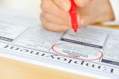 Hand mit rotem Feder-Markierungs-Job in der Zeitung lizenzfreie stockfotografie