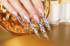 Hand mit schönen Nägeln auf Goldhintergrund Lizenzfreie Stockfotos