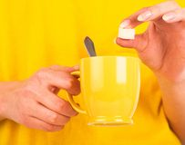 Hand mit Scheibe des Zuckers Stockfotos