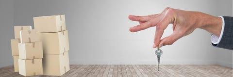 Hand mit Schlüssel gegen Raum 3d mit Kästen Stockbild