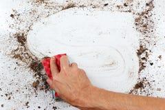 Hand mit Schwamm säubert schwer schmutzige Oberfläche Stockfoto