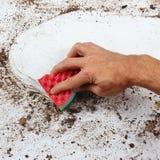 Hand mit Schwamm säubert sehr schmutzige Oberfläche Lizenzfreies Stockbild
