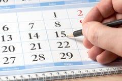 Hand mit schwarzem Bleistift auf Kalender Stockfotografie