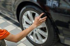 Hand mit schwarzem Schwammwachs auf Reifen Lizenzfreie Stockbilder