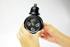 Hand mit schwarzer Alarmuhr Stockfoto