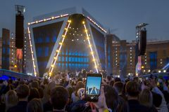 Hand mit Smartphoneaufnahmevideo/Foto am Live-Musik-Konzert, Schattenbilder der Menge vor hellem Stadium beleuchtet stockbilder