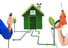 Hand mit Stecker und Hand mit Bohrgerät mit Hintergrund des grünen Hauses Stockbilder
