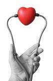 Hand mit Stethoskop und Herzen Lizenzfreie Stockfotos