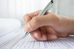 Hand mit Stift über Anmeldeformular stockfoto