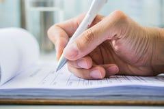 Hand mit Stift über Anmeldeformular Stockfotografie