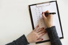 Hand mit Stift über Fragebogenanmeldeformular stockfotos