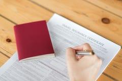 Hand mit Stift über Reise-Luftfahrtversicherungsanmeldeformular a stockfotografie