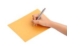 Hand mit Stiftschreiben auf dem Umschlag Stockbild