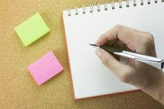 Hand mit Stiftschreiben auf gewundenem Notizbuch mit Notizblock lizenzfreie stockbilder