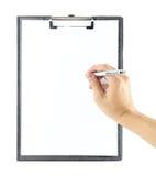 Hand mit Stiftschreiben auf Klemmbrett Lizenzfreie Stockfotos