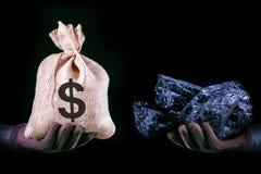 Hand mit Tasche mit Dollarbanknoten und Hand mit Kohlenstein Minenindustriekonzept mit Dollar und Kohle lizenzfreie stockfotos