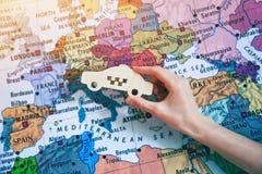 Hand mit Taxiautokennzeichen auf Karte Internationales Taxi Stockfotografie