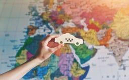 Hand mit Taxiautokennzeichen auf Karte Internationales Taxi Stockbild