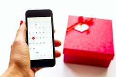 Hand mit Telefon und roter Geschenkbox am weißen backround Lizenzfreie Stockfotografie