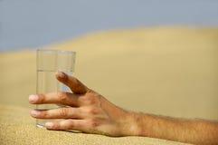 Hand mit Wasser in der Wüste Stockbilder