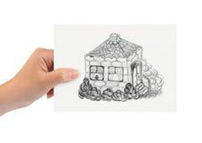 Hand mit Zeichnungshaus Stockbild