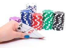 Hand mit zwei Assen und Stapel-Pokerchips Lizenzfreie Stockfotos