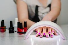 Hand mit zwei Frauen innerhalb der Lampe für Nägel auf Tabellenabschluß oben UVlampe Lizenzfreie Stockfotografie