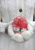 Hand in mittens holding a christmas gift. With red bow Royalty Free Stock Photos
