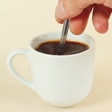 Hand mixing with spoon of prepared coffee in the cup Stock Photography