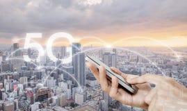 Hand mobiele smartphone met behulp van, en de draadloze technologie die van de netwerkverbinding in de stad, met het voorzien van royalty-vrije stock fotografie