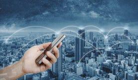 Hand mobiele smartphone met behulp van, en de technologie die van de netwerkverbinding in de stad Bedrijfsvoorzien van een netwer royalty-vrije stock afbeeldingen