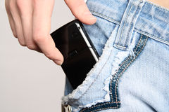 Hand with a mobile phone. The hand gets a mobile phone from a pocket of jeans Stock Images