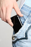 Hand with a mobile phone. The hand gets a mobile phone from a pocket of jeans Royalty Free Stock Photo