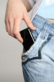 Hand with a mobile phone. The hand gets a mobile phone from a pocket of jeans Stock Photography