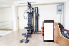 Hand with mobile phone on Fitness gym Royalty Free Stock Image