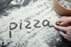 Hand mom and baby write the word `pizza` on the flour, black background. royalty free stock images