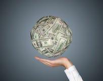 Hand with money ball Stock Photos