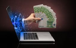 Hand with money coming out of a laptop. With sparkling effects stock photo