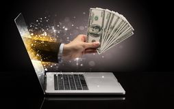 Hand with money coming out of a laptop. With sparkling effects royalty free stock image