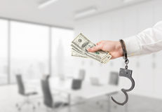 Hand with money in handcuffs Stock Image