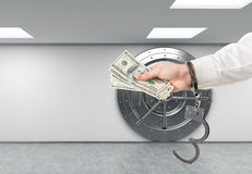 Hand with money in handcuffs Stock Images