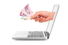 Hand with money out of laptop display Stock Image