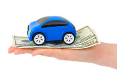 Hand with money and toy car. Isolated on white background Stock Photo