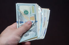 Hand with money from various counties Royalty Free Stock Photo