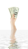Hand with money in the water Royalty Free Stock Images