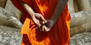 Hand of monk watching statue of buddha Royalty Free Stock Photo