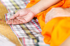 Hand monk. Hand of Monk`s praying and touching a holy thread for make a merit to dead person Royalty Free Stock Photos